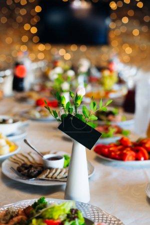Photo pour Une table de mariage avec de nombreux plats délicieux et un vase à fleurs avec une carte de visite - image libre de droit