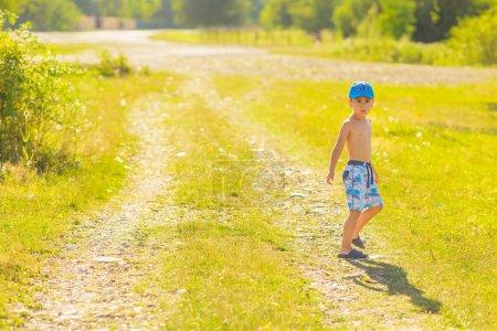 Photo pour Garçon par jour d'été debout sur un chemin de terre qui traverse le village - image libre de droit