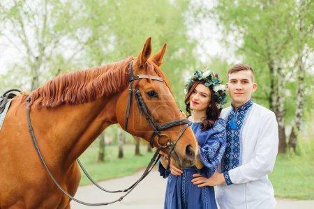Photo pour Le profil d'un beau cheval et de la fille qui le regarde et le tient pour une bride. la fille se tient près d'un gars qui étreint sa taille et regarde l'objectif de la caméra - image libre de droit