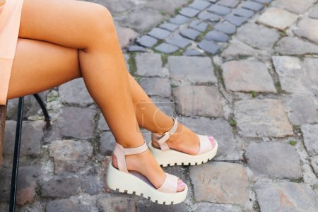 Photo for Close-up of a girl's legs who sitting on a bench. beautiful white sandals - Royalty Free Image