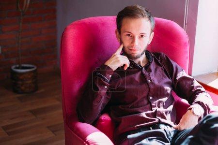 Photo pour Portrait de gars attrayant portant des vêtements formels élégants assis dans un fauteuil et regardant la caméra. - image libre de droit