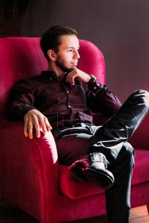 Photo pour Portrait conceptuel d'un jeune homme d'affaires prospère assis en studio dans un fauteuil sur une photo en noir et blanc. - image libre de droit