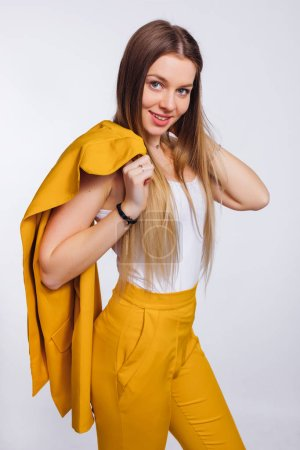 Photo for Girl with a long hair holds a yellow jacket on her shoulder. yellow trouser suit. - Royalty Free Image
