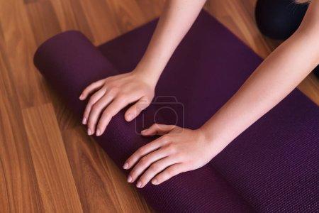 Photo pour Jeune fille de yoga roulant son tapis violet après avoir fait du yoga sur un plancher en bois. - image libre de droit