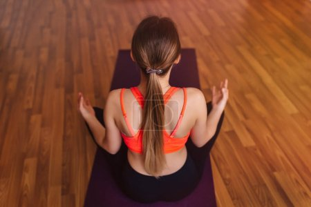 Photo for Rear view of a young woman practicing yoga and meditating. Concept of healing body and spirit. - Royalty Free Image