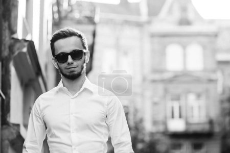 Photo for A young attractive bearded hipster man in sunglasses wearing a white shirt stands on a city street. black and white photography. - Royalty Free Image