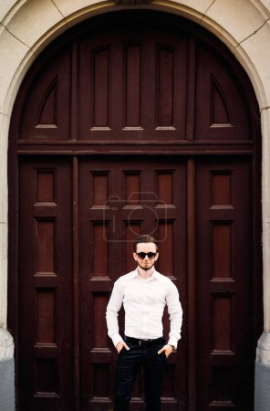 Photo for Young beard man posing on a background of building with wooden doors. fashion style and sunglasses. - Royalty Free Image