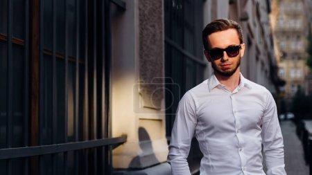 Photo pour Jeune beau barbu portant une chemise blanche et des lunettes de soleil est debout dans la rue de la ville. - image libre de droit