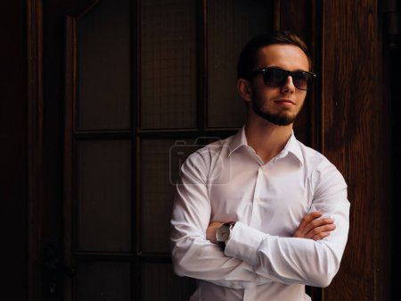 Photo for Portrait young guy with a beard in sunglasses and white shirt. studio, wooden door. - Royalty Free Image