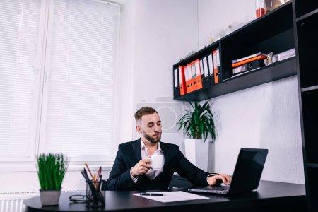 Photo pour Jeune homme avec une tasse de café travaillant sur ordinateur portable. Homme d'affaires travaillant à son bureau avec une tasse à thé. - image libre de droit