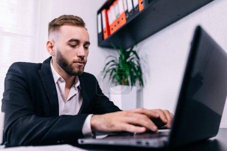 Photo pour Homme tapant à la main sur le clavier de l'ordinateur portable au bureau. Businessman travail et écrire rapport financier, navigation - image libre de droit