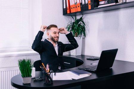 Photo pour Photo de l'homme d'affaires heureux au bureau près de l'ordinateur faire geste gagnant. - image libre de droit