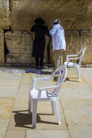 A religious orthodox Jew praying at wall while janitor sweeping nearby. Jerusalem, Israel.