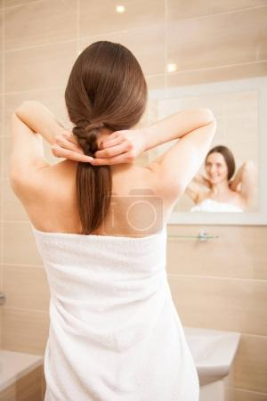 Smiling woman plaiting hair
