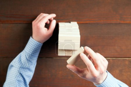 Male hands building with wooden blocks
