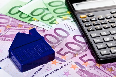 Cash, calculator and small house