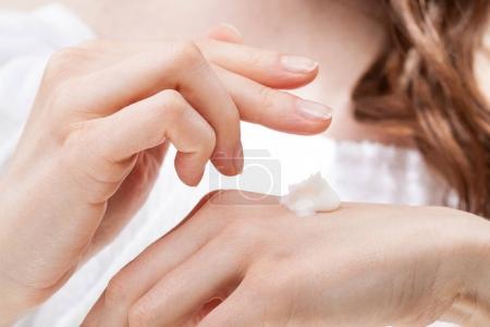 Woman hands applying hand cream