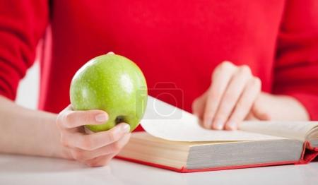 woman with book and apple