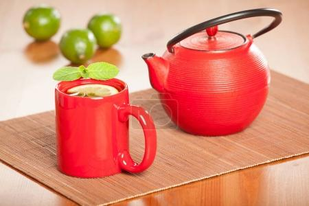 Teapot and cup of tea with lime and mint