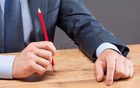 Businessman holding red pencil