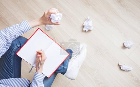 Woman writing in diary and crumpling pages