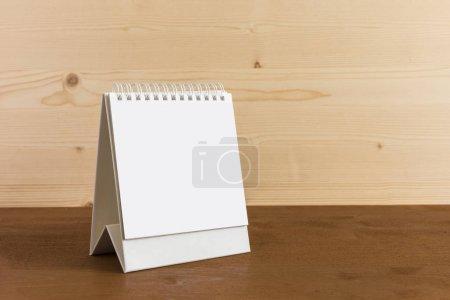White blank paper desk spiral calendar on wood background