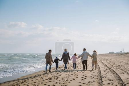 Photo for Back view of big multigenerational family walking together on seashore - Royalty Free Image
