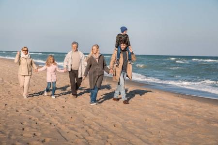 Photo pour Parents de ferroutage fils tandis que grands-parents, main dans la main avec la petite-fille, marchons ensemble au bord de mer - image libre de droit