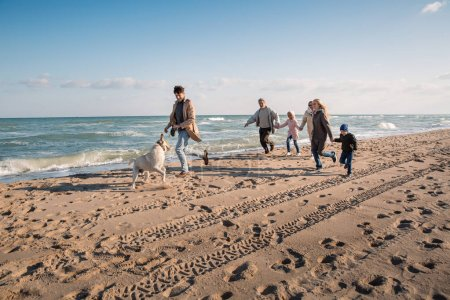 Photo for Big multigenerational family running with labrador dog on beach at seaside - Royalty Free Image