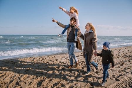 Photo pour Héhé, pointant quelque part en marchant ensemble au bord de mer à l'automne - image libre de droit