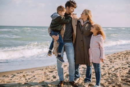 Photo for Happy family hugging together on seashore in autumn - Royalty Free Image
