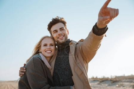 Photo for Smiling couple embracing while man pointing somewhere on beach in autumn - Royalty Free Image