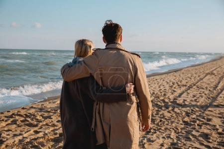 couple embracing and walking on seashore