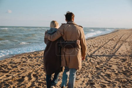 Photo for Back view of couple hugging and walking together on seashore in autumn - Royalty Free Image