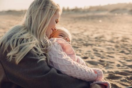 Photo for Happy mother hugging her daughter on sandy beach - Royalty Free Image