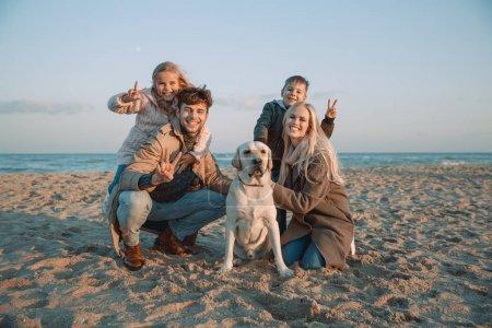 Photo pour Héhé avec chien labrador montrant des symboles de la paix au bord de mer - image libre de droit