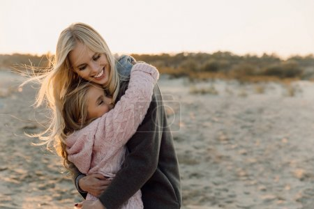 Photo for Happy mother embracing her daughter on seashore - Royalty Free Image