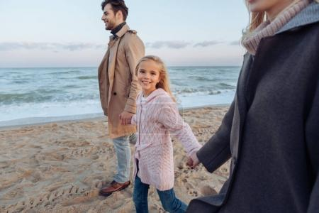 Photo for Daughter holding hands with parents while walking on seashore in autumn - Royalty Free Image