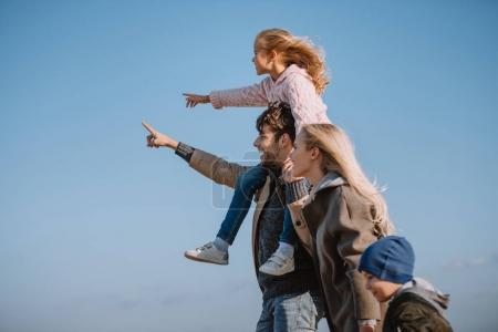 Photo for Parents spending time with their kids and pointing somewhere - Royalty Free Image