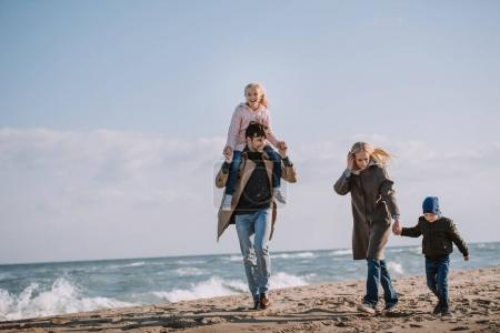 Photo for Parents walking with kids on seashore in autumn - Royalty Free Image