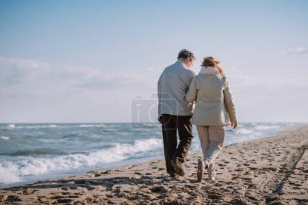 Photo pour Vue arrière du couple de personnes âgées passant du temps ensemble et marchant sur le rivage en automne - image libre de droit