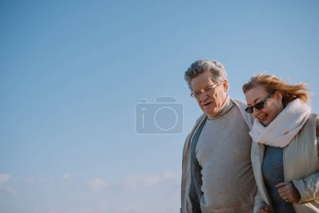Photo for Senior couple in eyeglasses hugging and walking together - Royalty Free Image