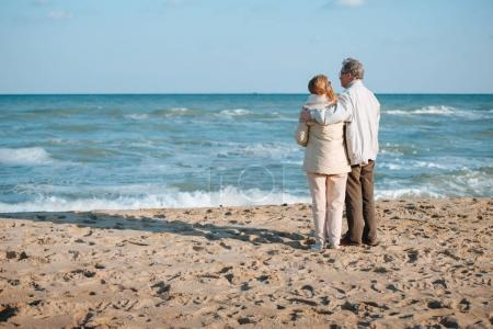 Photo for Senior couple spending time together and hugging on seashore in autumn - Royalty Free Image