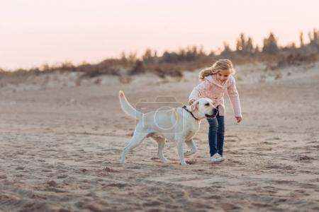 child running with dog on beach