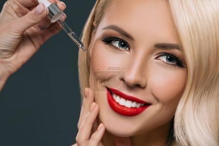 Photo pour Belle femme blonde appliquant le sérum sur son visage, d'isolement sur le gris - image libre de droit