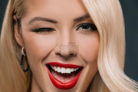Photo for Beautiful blonde winking woman, isolated on grey - Royalty Free Image