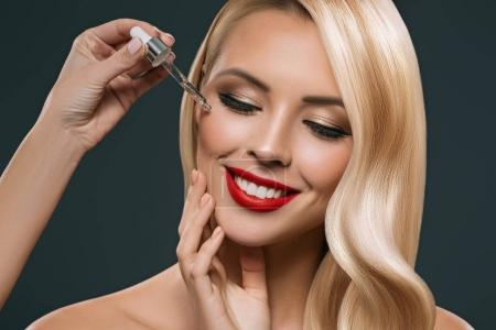 beautiful blonde girl applying treatment from pipette on face, isolated on black