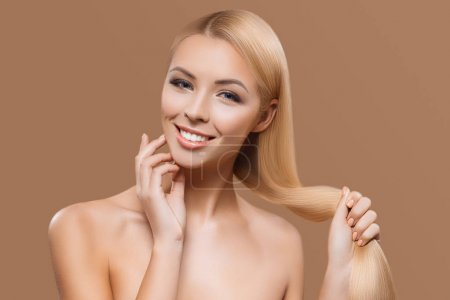 portrait of beautiful blonde long hair girl isolated on beige
