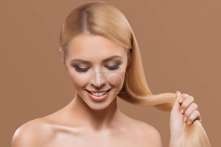 portrait of beautiful blonde long hair girl with closed eyes isolated on beige