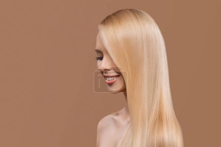 Photo for Side view of beautiful girl with blonde long hair and closed eyes isolated on beige - Royalty Free Image